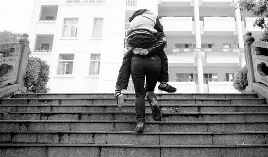 韦慧娟背着儿子,爬上磐安中学的台阶