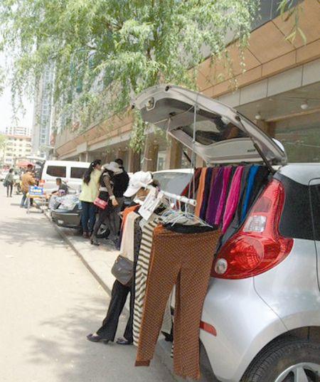 图为柳北南肖墙附近汽车占道练摊。