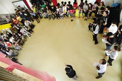 """昨日,在""""老师长期殴打孩童""""的当事幼儿园内,朝阳区教委、园方和警方正向孩子家长们说明情况。本版摄影/新京报记者 尹亚飞"""
