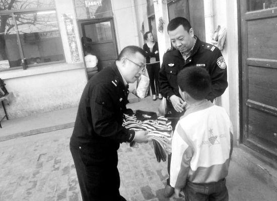 派出所所长李宏宇(左一)、副所长李建军(右一)带着衣服看望小新源