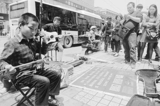 图为:盲童胡三金在街头表演