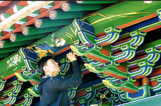 月8日,古建修缮人员为省城鼓楼广场西侧牌楼彩绘五彩汉纹锦彩画。