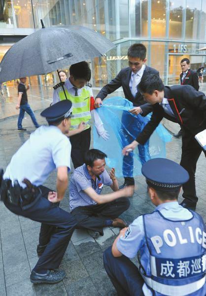6月13日,成都大慈寺附近,保安张光建和同事及民警帮助坐在雨中的老赵。
