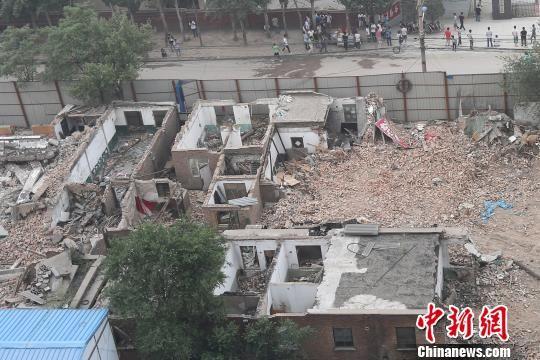 王先生的房屋被铁皮和建筑垃圾围困。 武俊杰 摄