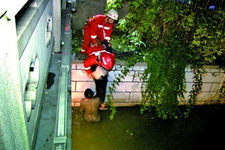 消防队员将男子和狗救上岸。