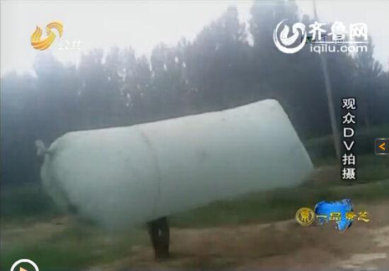 村民表示由于灌装天然气不要钱,也就顾不上危险了,图为一村民背着装了天然气的大塑料袋回家(视频截图)