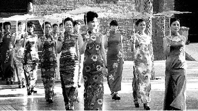 少林寺山门前,10余名女子手撑素油伞,身穿颜色艳丽的旗袍,迈着猫步在庙宇前走秀。