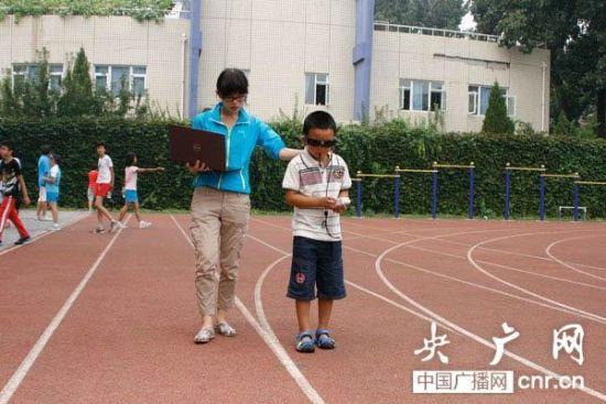 """小斌斌戴着""""电子眼""""在学校的操场上训练。(记者谢梦瑶_摄)"""