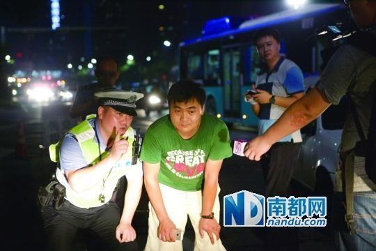 昨晚,深圳交警让一名男司机半蹲在自己车头前观察远光灯的威力。(南都记者 王子荣 摄)