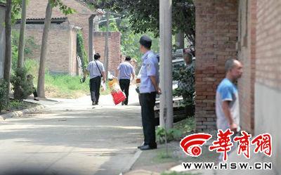 昨日,西安市阎良区谭家村,警方在事发的孙某家里勘查现场后,将提取的物证带走华商报记者 黄利健 摄