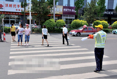 义务交通管理员指挥行人过马路