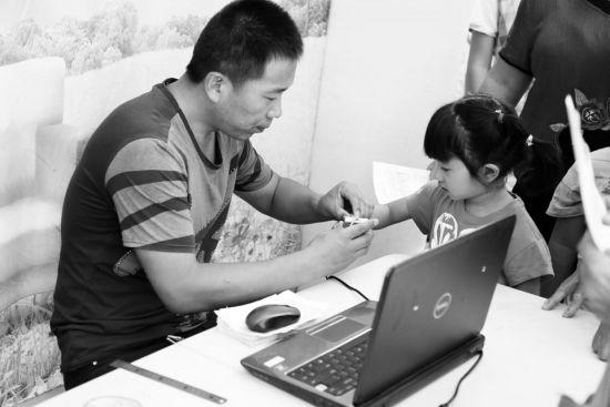 工作人员在为儿童录入指纹。