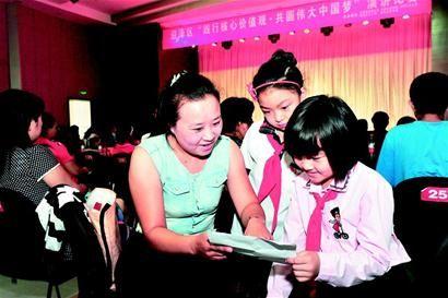 东岗小学的郭雅琪演讲前在妈妈的指导下熟悉讲稿。