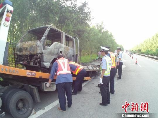 山西一辆载有液化气罐体的白色轻型货车日前在高速路上发生自燃,致使车辆烧成空壳,民警正在处理。 任静 摄
