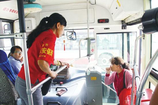9月2日,山纺下岗职工吴洁琴正在855公交车上做安全疏导。