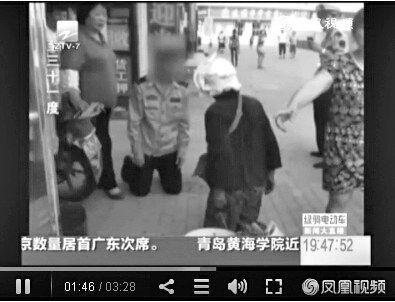 城管与卖菜大妈当街互跪。视频截图