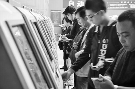 旅客在自助取票机上取票 记者 冯永伟 摄
