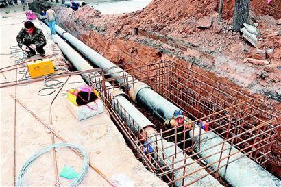 图为10月9日,施工人员在王村北街挖掘沟槽、铺装热力管线。梁琛 摄