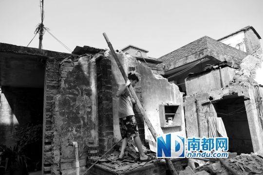 10月29日上午,叶村东在清理压在自家房子上的横梁。作为一个养子,他撑起整个家庭。 南都记者 梁清 摄