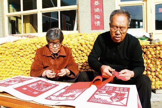 赵宏斌(右)和老伴在院子里剪纸。 褚 震摄