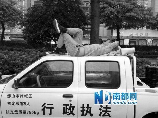 季华五路人行天桥附近,一名小贩爬上禅城祖庙城管执法车车顶。南都记者 冯雷亮 摄