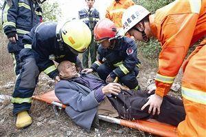 消防队员将老人抬上担架 通讯员供图